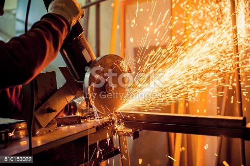 A man working with electric grinder tool  on steel structure in factory, sparks flying