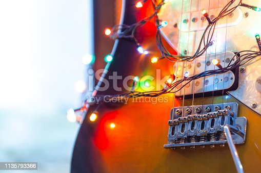 Electric guitar in bright colors of festive lights of the garland