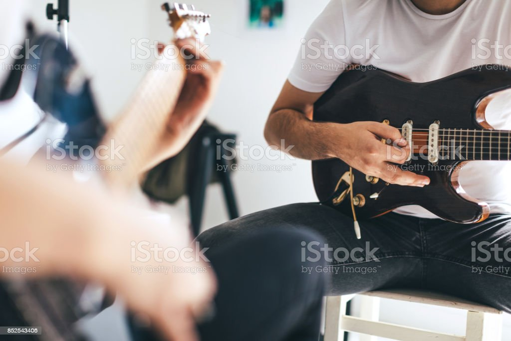 Electric guitar in hands of young woman stock photo