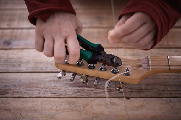 Electric guitar maintenance, seting up strings, close-up stock photo