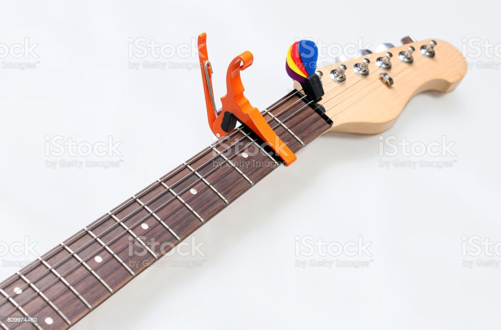Electric guitar neck with a capo and picks stock photo