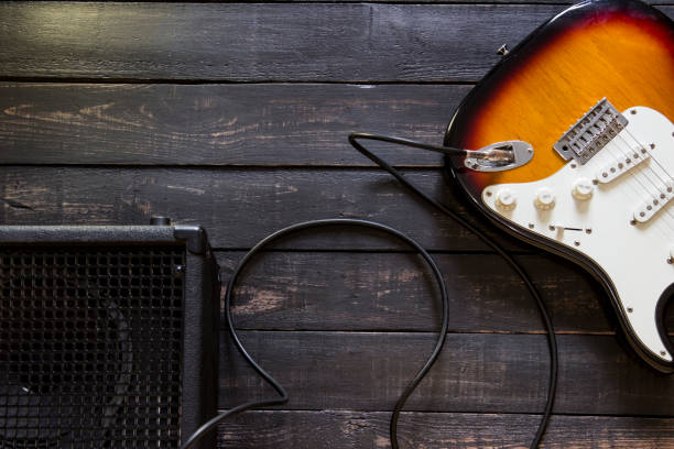 Electric guitar with amplifier connected by cable on wooden background stock photo