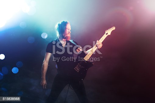A fashionable young man with long hair and beard plays a black electric guitar at a live music venue, orange and blue stage lights illuminating the scene.  He holds his guitar out toward the audience, a look of passion on his face as he feels the music.  Horizontal with copy space.
