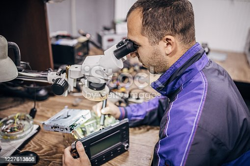 One man, Electric hand tool in hands of repairman, he using microscope at workshop.