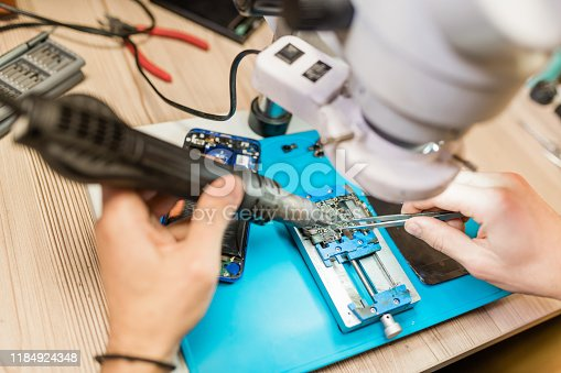 483784268 istock photo Electric handtool and tweezers in hands of repairman using microscope at work 1184924348
