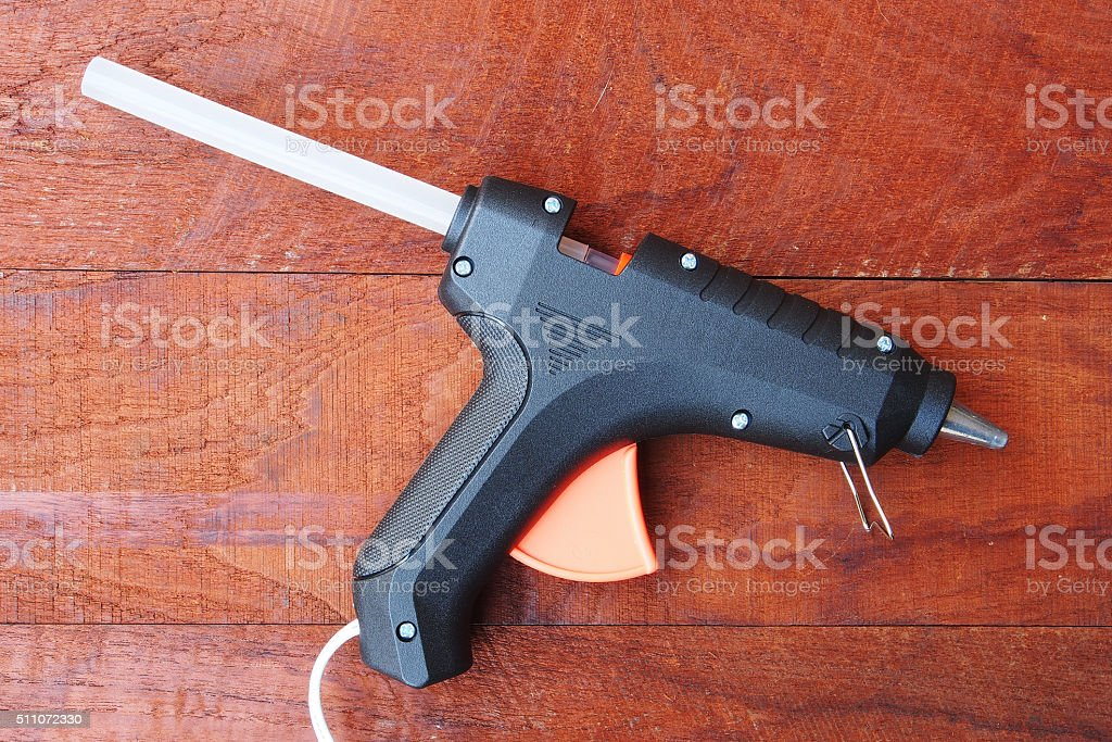Electric hot glue gun on a wood background stock photo