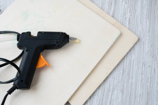 Electric hot glue gun on a wood background. the concept of repair or creativity background Electric hot glue gun on wood background. the concept of repair or creativity background affix stock pictures, royalty-free photos & images