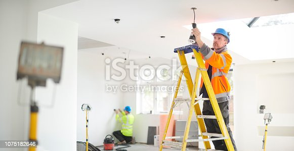 electrician installing downlights
