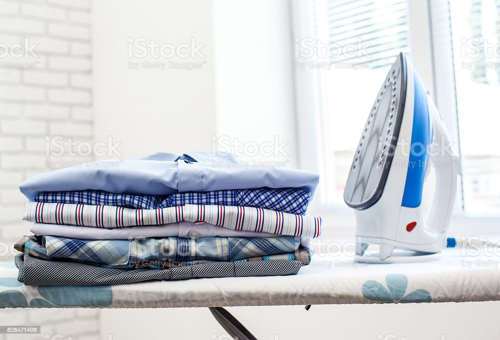 Electric iron and shirts stock photo