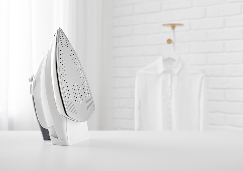 Electric iron on table in blurred room with clothes rack