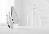 istock Electric iron on table in blurred room with clothes rack 1280518667