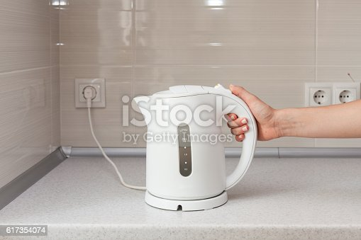 istock Electric Kettle in hand on the background of the kitchen. 617354074