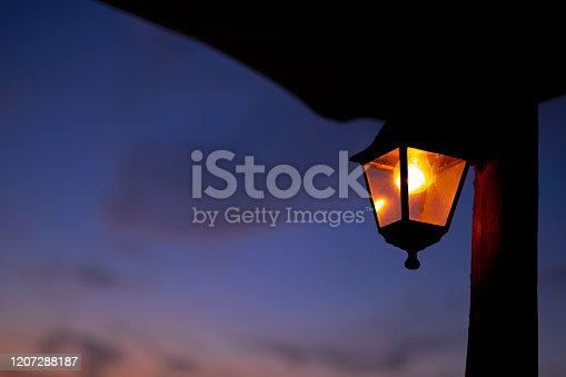 Close-up with an electric lamp turned on hanging on wooden pile. In background blue and orange sky.