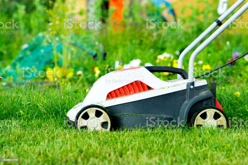 electric lawn mower on green grass stock photo