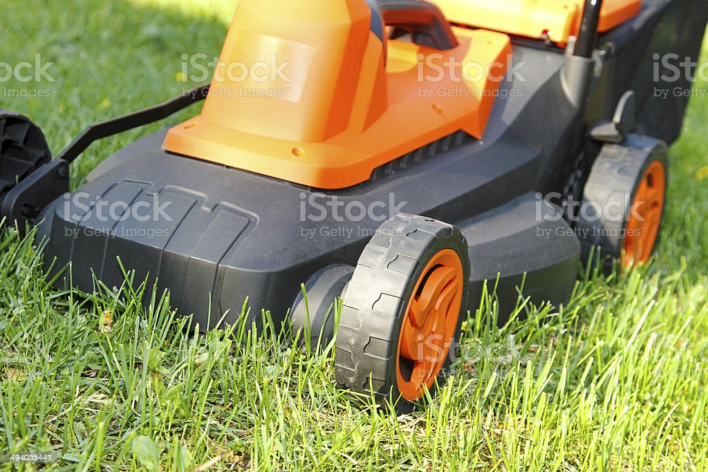 electric lawnmower on green grass stock photo
