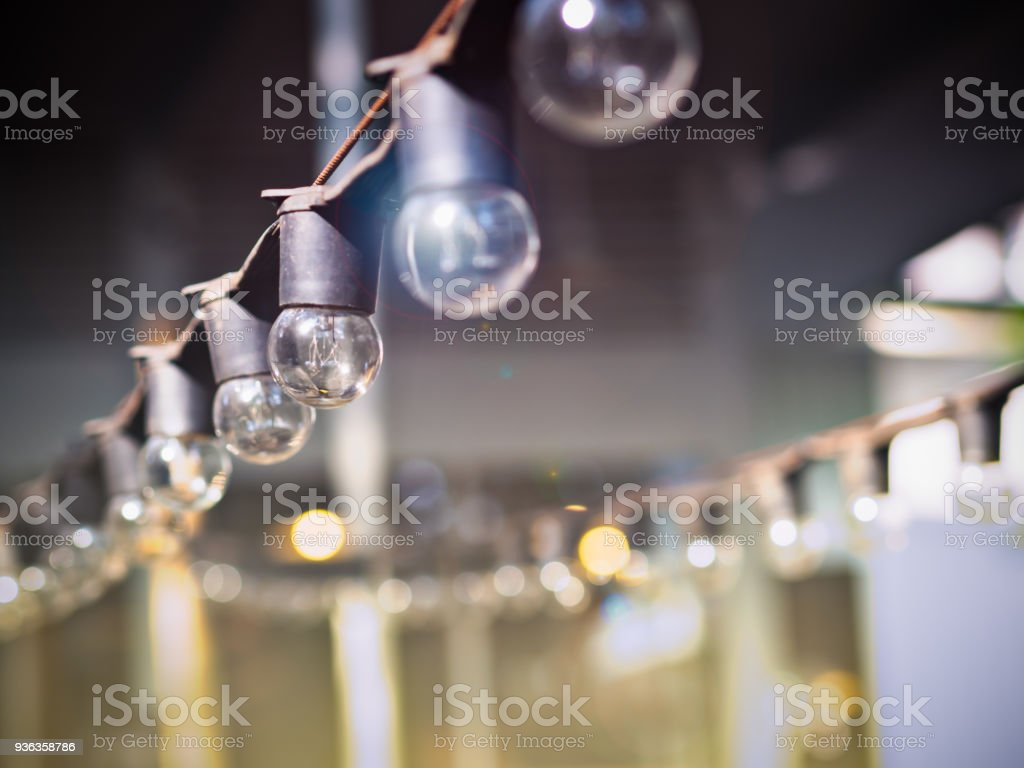 Electric light bulbs on sling for party light decoration or outdoor garden decoration stuffs with beautiful sunset or sunrise flare lights stock photo