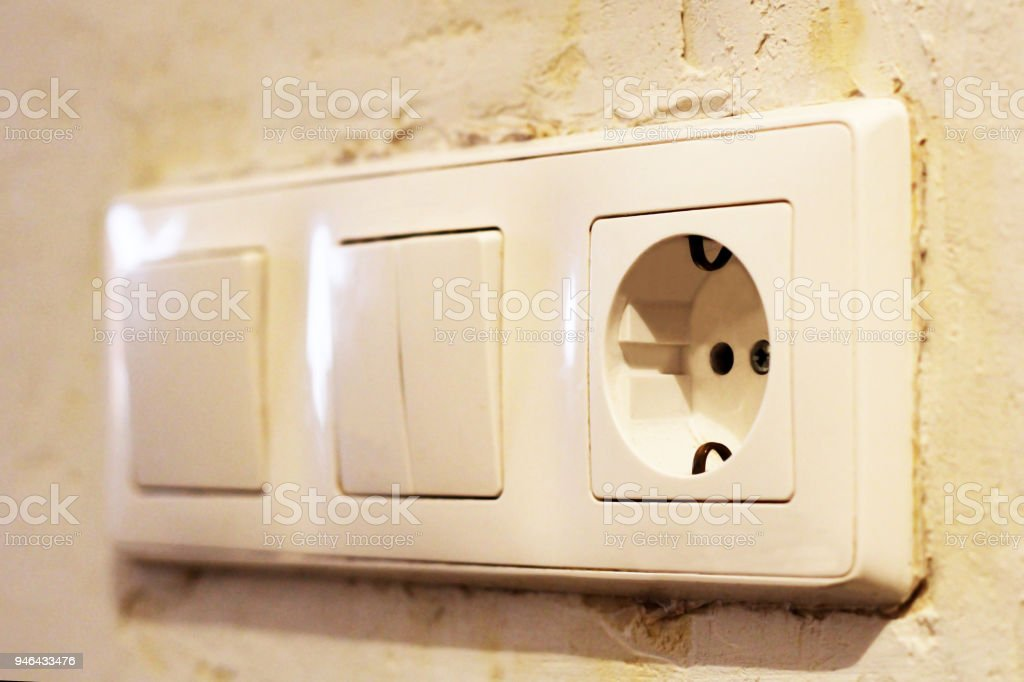 Electric Light Switch And Socket On The Empty Wall