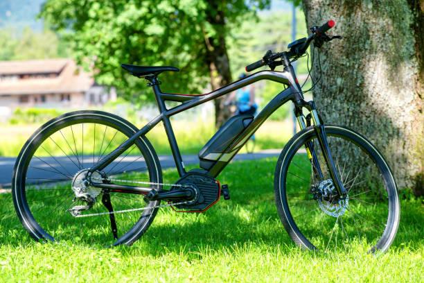 elektro-mountainbike auf dem rasen - elektrorad stock-fotos und bilder
