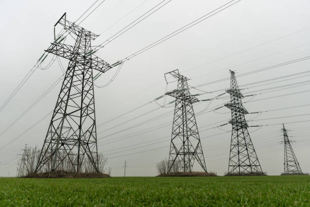 Electric network of pylons against a cloudy sky and a green meadow