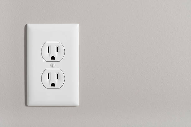 Electric Outlet A white home electrical outlet on a light grey wall. electric plug stock pictures, royalty-free photos & images