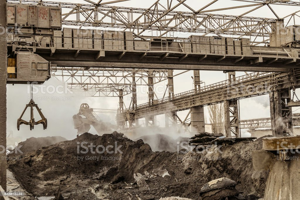 Electric overhead crane with mechanical multivalve clamshell grab in outdoors industrial plant shop. Slag dump. Waste of metallurgical industry. stock photo