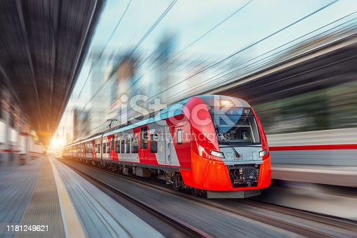 Electric passenger train drives at high speed among urban landscape