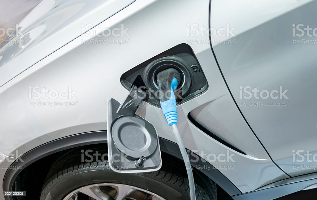 Electric plug-in hybrid car charging stock photo