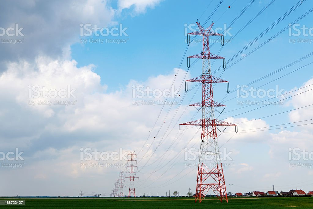Electric pole under cloudy sky stock photo