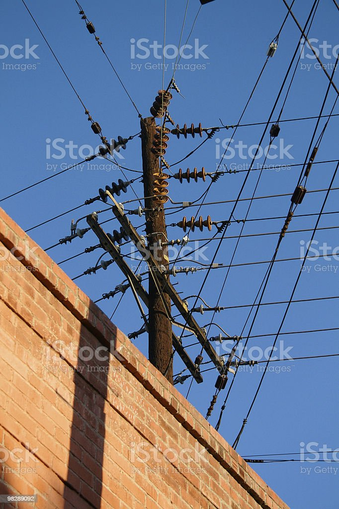 Electric pole with brick wall & maze of wires royalty-free stock photo