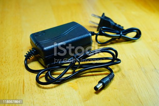 Black electronic battery charger for mobile phone on wooden floor.