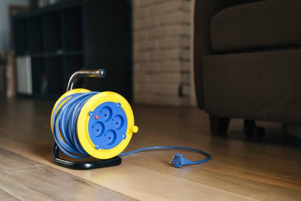 extension d'alimentation électrique avec le fil bleu et jaune tambour à l'intérieur de l'appartement. électricité et design. - rallonge électrique photos et images de collection