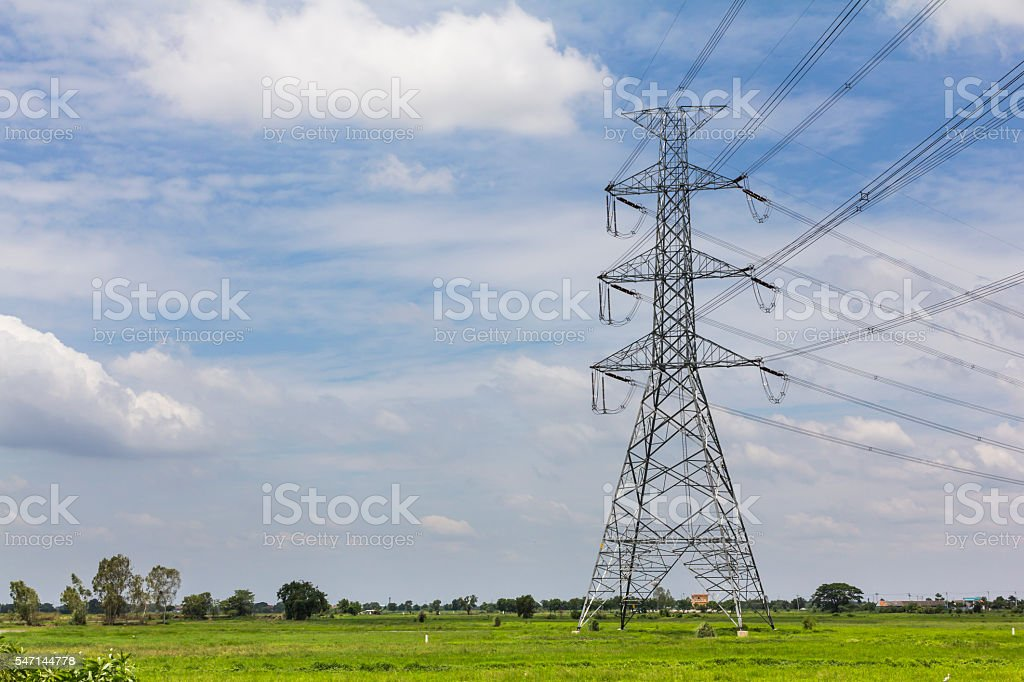Electric power transmission in the field against the blue sky stock photo
