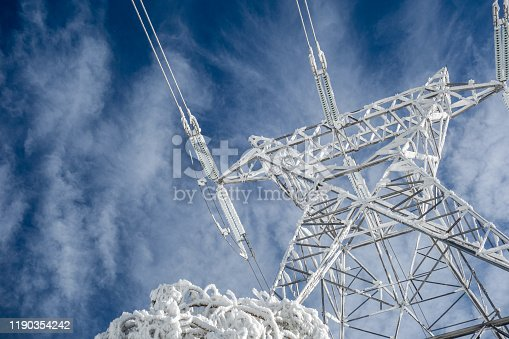 High voltage electric tower on a snowy day in the mountains