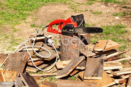 Electric saws and chainsaw. Electric saw chain on the background of sawn timber. The concept of processing wood to produce fuel