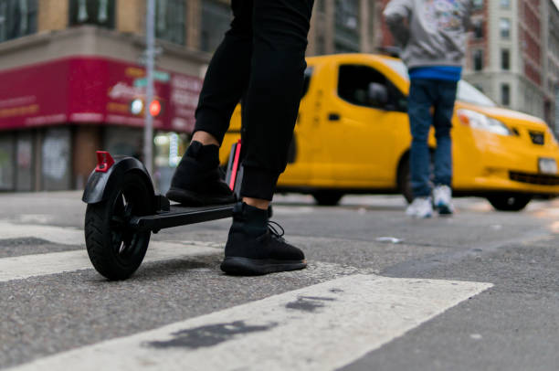 electric scooter and yellow cab - electric push scooter stock photos and pictures