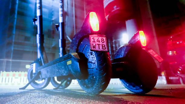 Scooter électrique à louer garé avec feu arrière allumé, dans le centre-ville de Hambourg la nuit. - Photo