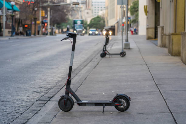 Electric Scooter on Sidewalk in Downtown District stock photo