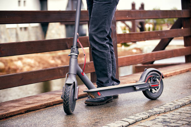 electric scooter stands on a bridge in the street. - electric push scooter stock photos and pictures