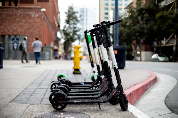 electric scooters for rent - electric push scooter stock photos and pictures