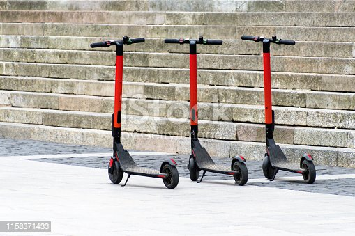 istock Electric scooters in row on the parking lot. City bike rental system, public kick scooters on the street 1158371433