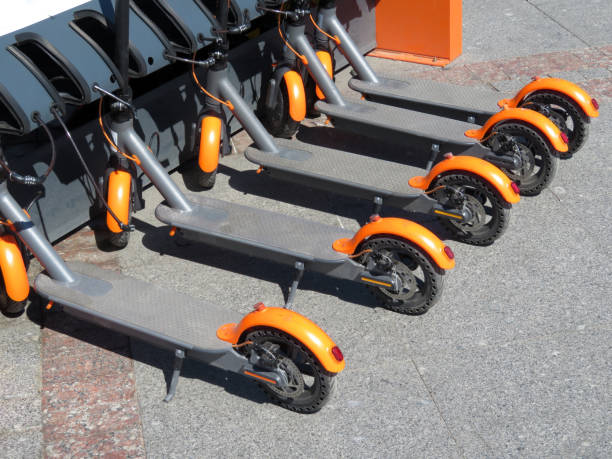 electric scooters in row on the parking lot - electric push scooter stock photos and pictures