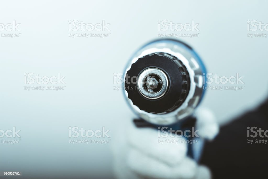 Electric screwdriver in hand at white desk background foto stock royalty-free