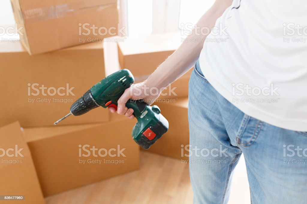 Electric screwdriver in the man hand at home background with boxes....