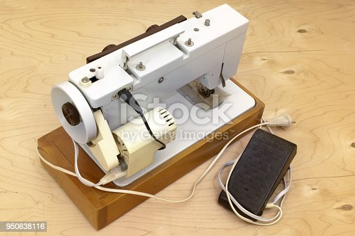 istock electric sewing machine, heavy duty with side electric motor and foot controller - black pedal. set on a wooden platform 950638116