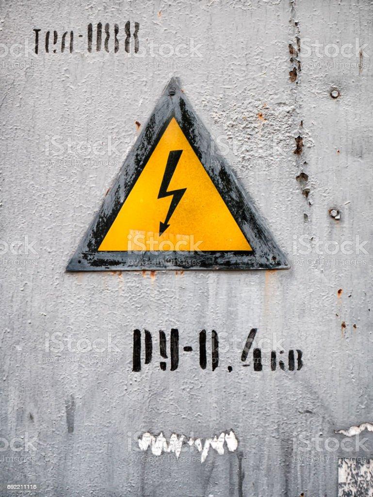 Sinal de perigo de choque elétrico na superfície de metal enferrujado. - foto de acervo