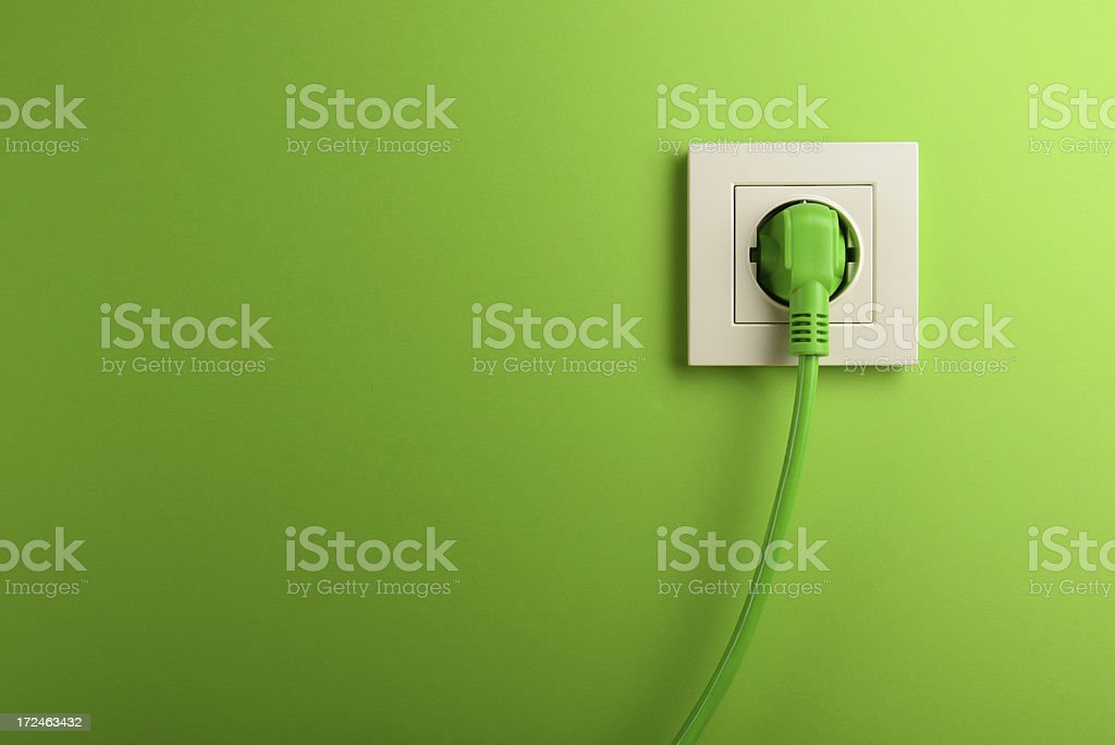 Electric socket in on green wall stock photo
