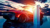 Red sports car is parked next to a charging station where the electric car can its batteries charged. The sun is setting in the horizon. The ground looks like a circuit board.