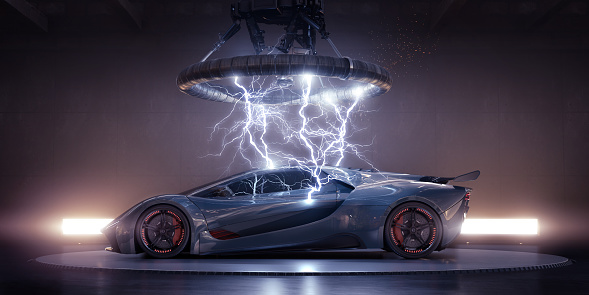Side view of a generic blue-grey sports car with orange highlights parked on a turntable in an industrial building under a large  coil, from which multiple strikes of electrical lightning are emanating, striking the bodywork of the vehicle. The has lights behind it, and a thin haze.