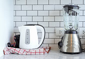 Electric stainless steel kettle and blender on ceramic with plug in kitchen room at home modern white background