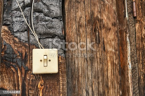 1015604978 istock photo Electric switch on the very old charred wooden wall 1220444083